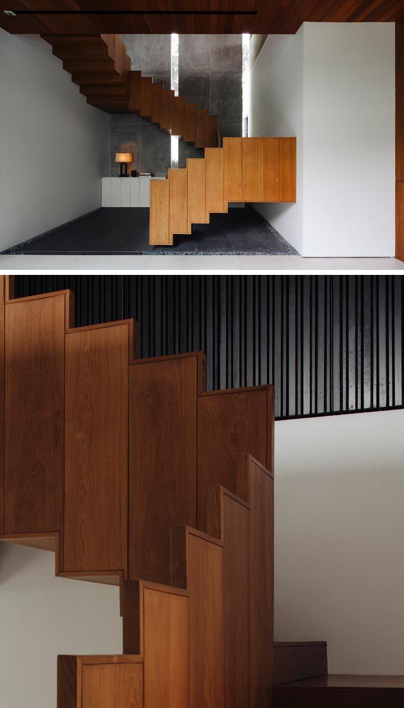 Ming Architects a conçu une maison à Singapour, et l'une des caractéristiques les plus marquantes de la maison est un escalier flottant en bois et son garde-corps. #FloatingStairs #WoodStairs #ModernStairs #WoodGuardrail #StairDesign #TeakStairs