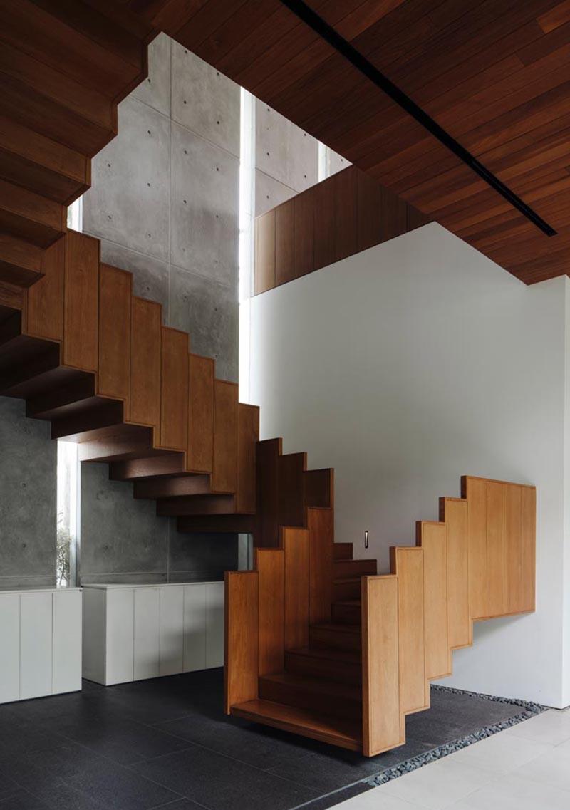 Ming Architects a conçu une maison à Singapour, et l'une des caractéristiques les plus marquantes de la maison est un escalier flottant en bois et son garde-corps. #FloatingStairs #WoodStairs #ModernStairs #WoodGuardrail #StairDesign #StairHandrail
