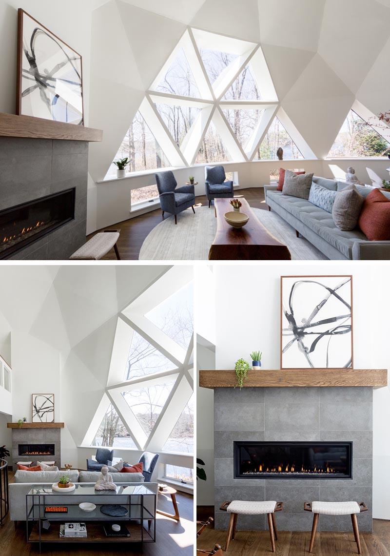 L'intérieur récemment mis à jour de cette maison en forme de dôme géodésique présente des murs d'un blanc éclatant et un mobilier moderne, comme dans le salon.  La cheminée, qui se trouve à côté d'une grande section de fenêtres, a un contour en calcaire surmonté d'un manteau de chêne personnalisé qui complète le plancher de bois franc.  #GeodesicDome #LivingRoom #Fireplace #TriangleWindows