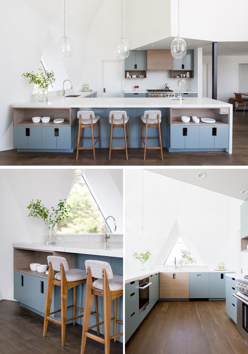 La cuisine ouverte dans cette maison de dôme géodésique rénovée présente des armoires personnalisées qui se composent d'un mélange de façades de dalles bleues et en bambou, avec des découpes pour les poignées.  Un comptoir et un dosseret en quartz complètent l'espace et le gardent lumineux.  #ModernKitchen #BlueKitchenCabinets #QuartzCountertop #GeodesicDomeInterior