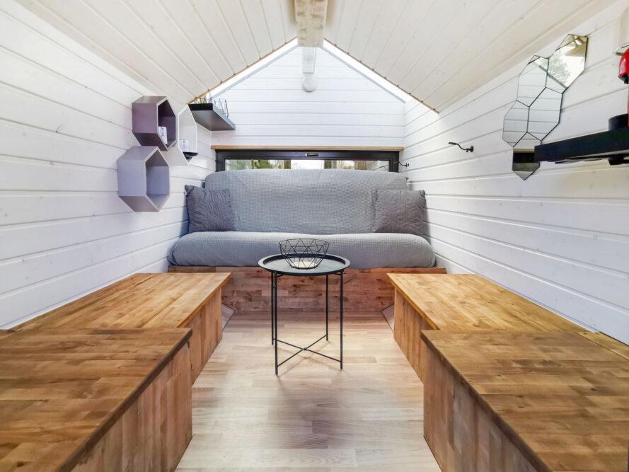 minuscule intérieur de cabine avec des murs blancs, des bancs en bois et un canapé gris