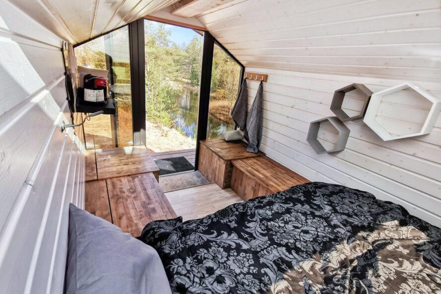minuscule intérieur de cabine avec lit gris, bancs en bois et un mur d'extrémité en verre