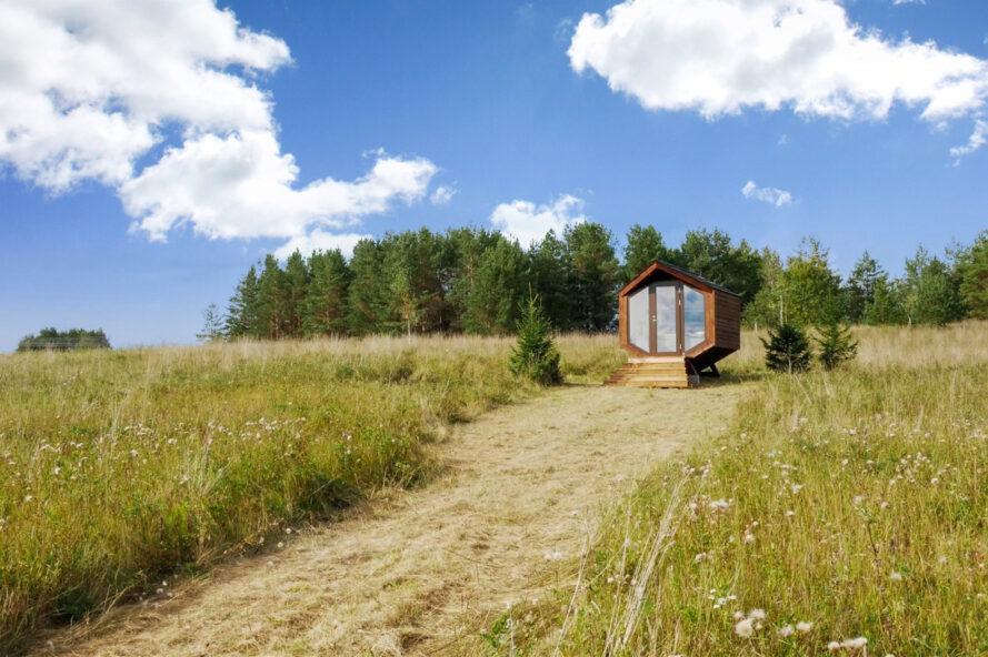 cabine en bois angulaire avec porte vitrée avec une forêt en arrière-plan