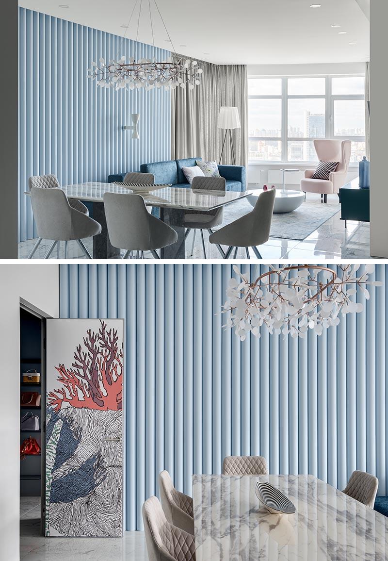 Conçu comme un moyen d'ajouter de la texture à la pièce, ce mur d'accent bleu doux est fait de panneaux qui ont une finition nervurée, permettant à la lumière naturelle de créer des ombres en constante évolution sur le mur. #SoftBlueInterior #BlueAccentWall #TexturedAccentWall #InteriorDesign #Blue #LivingRoom
