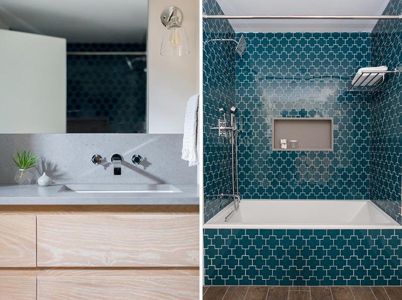 Dans cette salle de bain moderne, un comptoir en quartz se trouve au-dessus d'une vanité en bois sur mesure, tandis que le carrelage croix suisse sarcelle foncé a été utilisé pour ajouter un punch de motif et de couleur, et une niche de douche fournit un élément d'étagère.  #ModernBathroom #CrossTile #TealTile