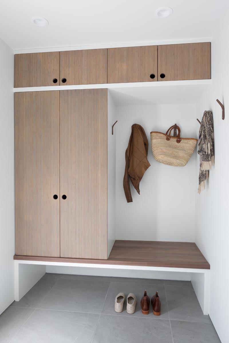 Ce vestiaire moderne a des armoires en bambou personnalisées avec un banc intégré.  Pour garder son design minimal, il y a des trous pour les doigts au lieu de la quincaillerie et des crochets en bois sur le mur.  #Mudroom #ModernMudroom #EntrywayIdeas