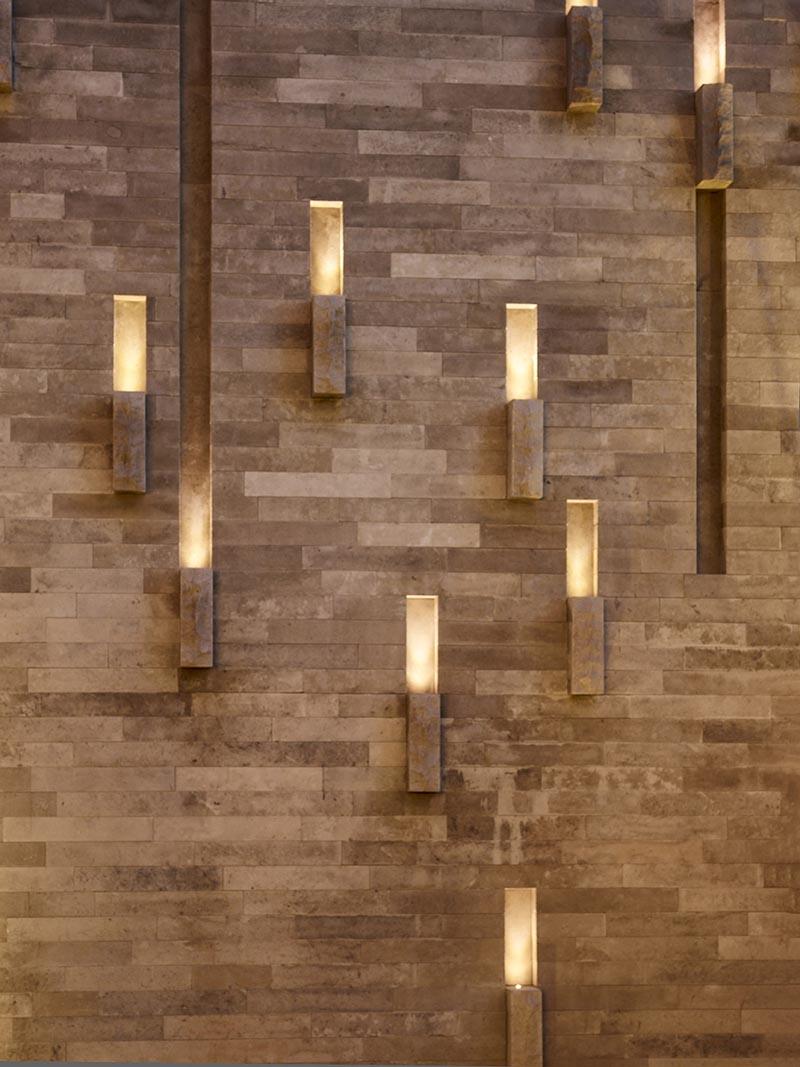 Des encoches sur la face d'un mur extérieur créent des canaux de lumière ponctués d'accents de pierre, créant une lumière sculpturale semblable à une lanterne la nuit. #OutdoorLighting #LandscapeDesign #Landscaping