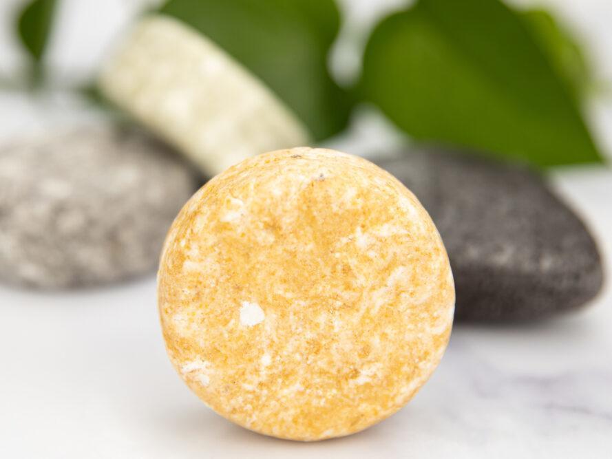 Barre de savon jaune ronde au premier plan avec des barres de savon gris, crème et noir en arrière-plan