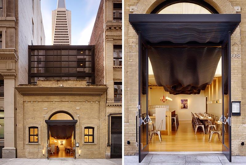 Le détail sculptural noir ondulant saisissant se déplace de l'intérieur du restaurant jusqu'à la façade, où il couvre l'entrée et ajoute un élément moderne au bâtiment historique. #BuildingFacade #SculpturalFacade #RestaurantDesign