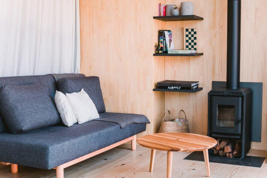 intérieur en bois avec canapé gris et poêle à bois