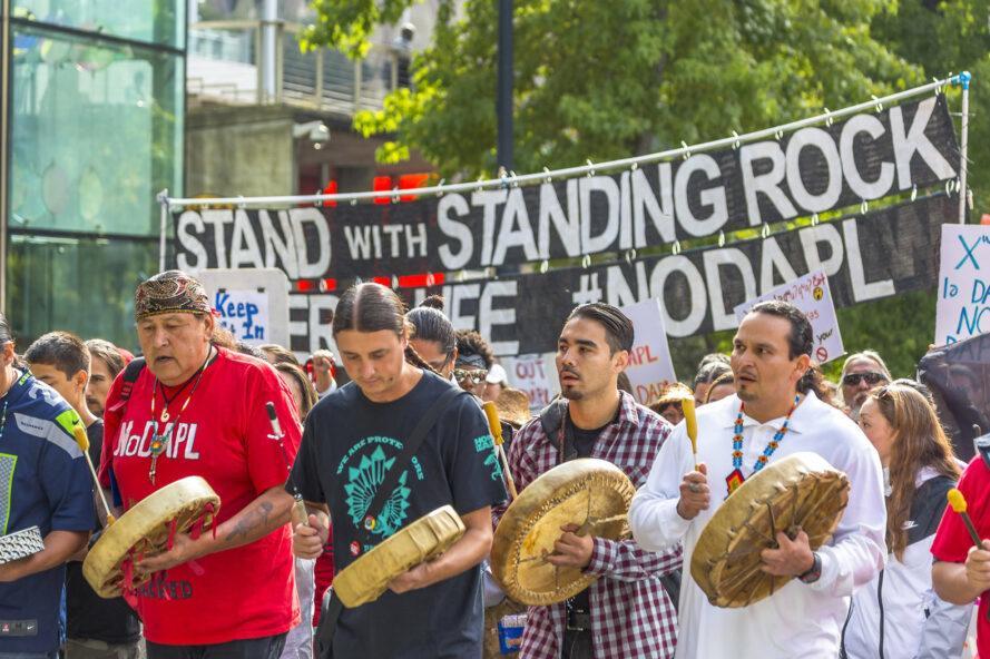 """un groupe de quatre personnes se tient devant une foule et tient des tambours, avec un signe dans la lecture de fond """"Stand avec Standing Rock"""""""