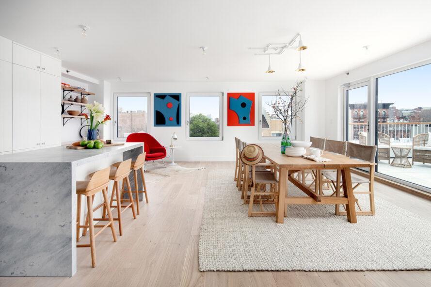 appartement décloisonné avec longue table à manger en bois et îlot de cuisine en marbre