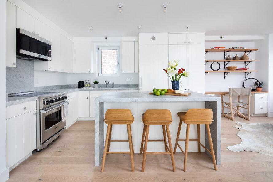 cuisine blanche avec appareils en acier et îlot en marbre