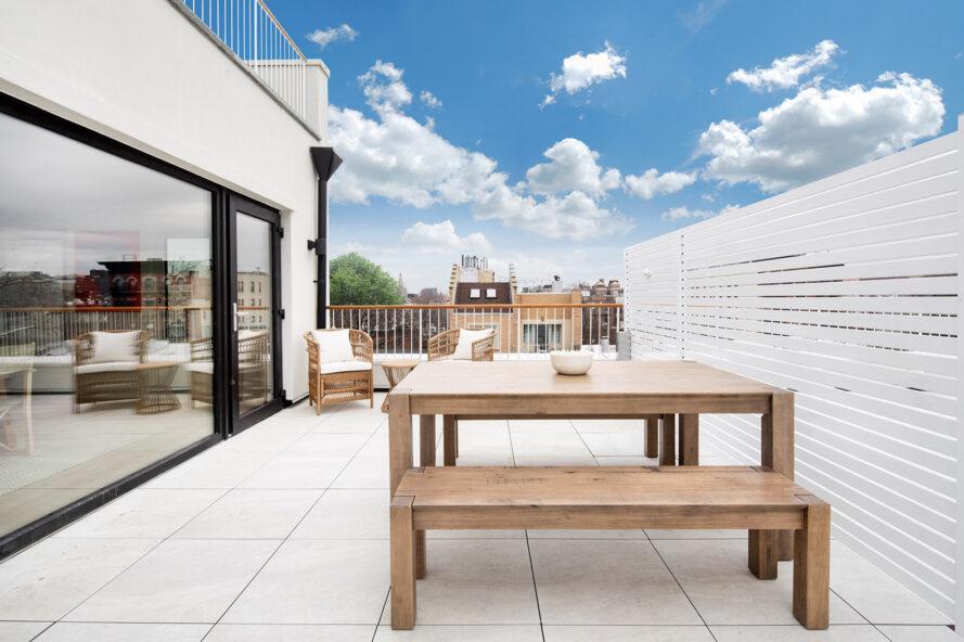 terrasse extérieure fermée avec table et bancs en bois