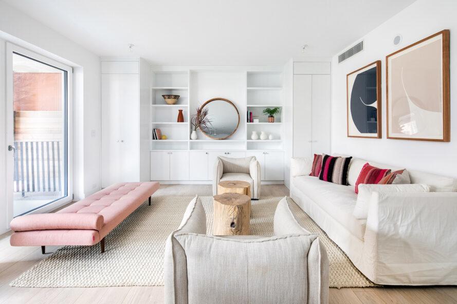 salon avec méridienne rose, canapé blanc et étagères encastrées blanches