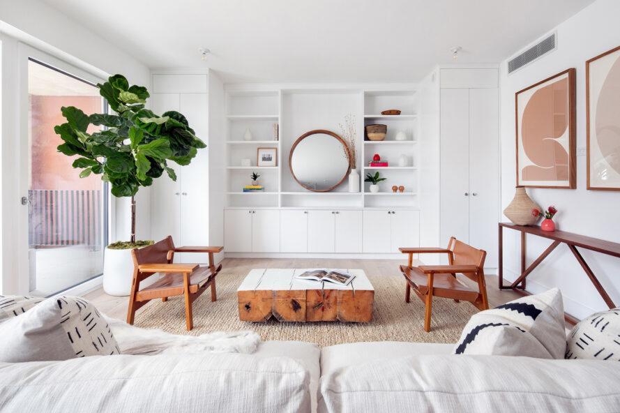 chaises marron et canapé blanc dans une salle blanche avec étagères intégrées