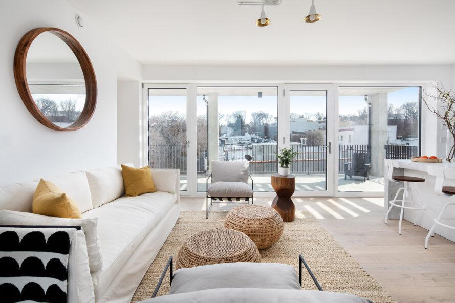 Canapé blanc et tables en osier à côté du mur de portes coulissantes en verre révélant une vue de New York