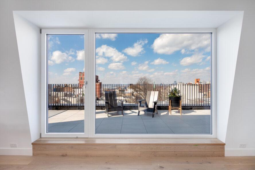 grande porte coulissante en verre sur un balcon avec une table et des chaises