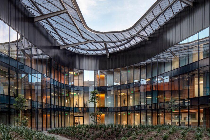 un bâtiment en forme de V avec un toit en aluminium en surplomb et une façade vitrée