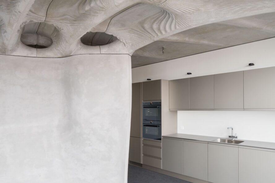 Armoires de cuisine grises dans une salle en béton avec plafond ondulé