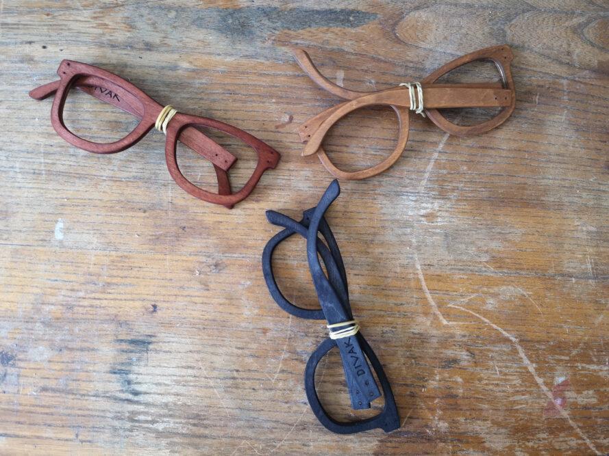 trois paires de montures de lunettes de soleil en bois sans lentilles sur une table en bois