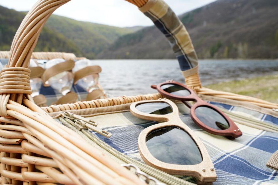 deux paires de lunettes de soleil en bois dans un panier de pique-nique