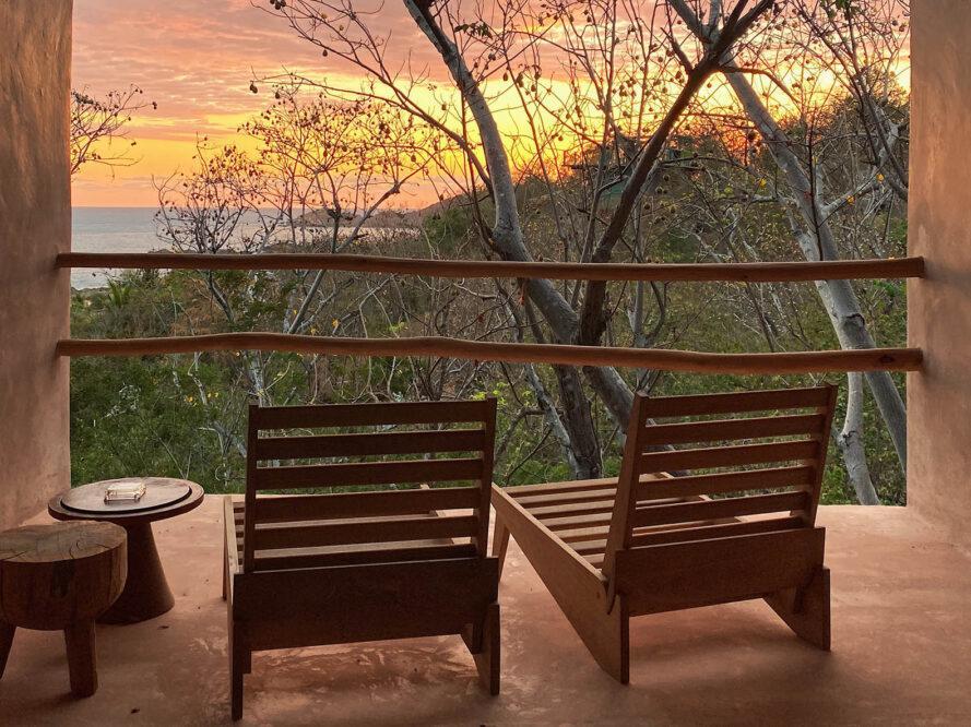 deux chaises en bois et deux courtes tables rondes à gauche devant deux bars qui protègent une terrasse avec vue sur le coucher de soleil dans la jungle.
