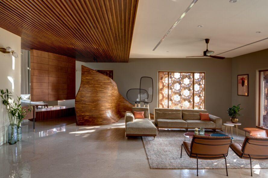 un salon avec des éléments en bois, y compris un diviseur en forme de vague qui sépare le coin télévision et le coin salon avec le canapé en forme de L.
