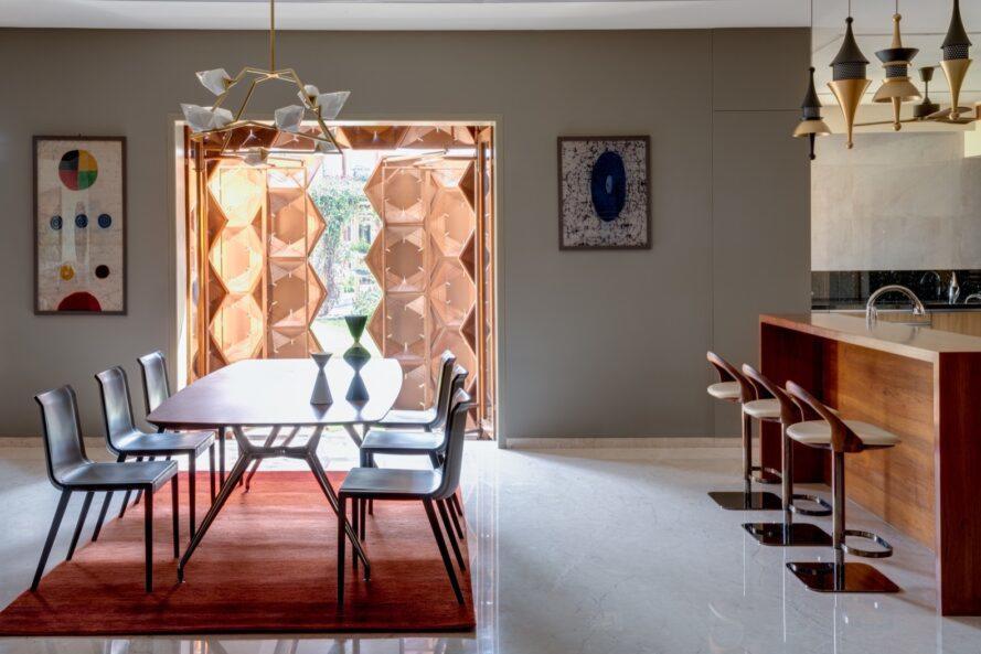 une salle à manger intérieure avec une fenêtre en nid d'abeille.  l'art abstrait est suspendu de chaque côté de la fenêtre.  une table à manger avec des chaises se trouve au milieu de la pièce, avec un tapis rouge-orange en dessous.  à droite, un bar en bois avec trois tabourets.