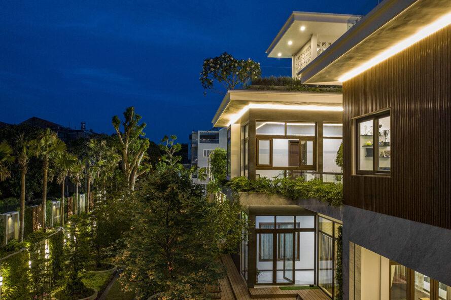 à gauche, divers arbres et verdure.  à droite, une maison à plusieurs niveaux éclairée la nuit, dotée de grandes fenêtres