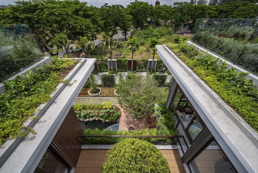 toits verts avec une cour entre eux et un jardin visible au rez-de-chaussée.