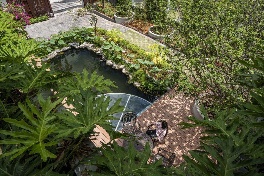 un étang entouré de verdure.  une personne est assise à une table à proximité, donnant sur l'étang.