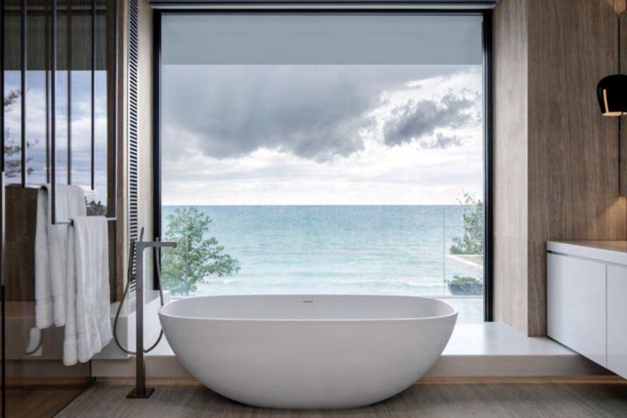 Baignoire autoportante à côté du mur de verre révélant une vue sur un lac