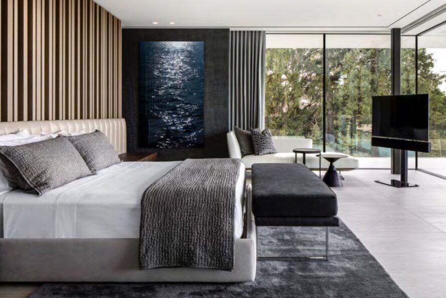 grand lit blanc face à un mur de verre