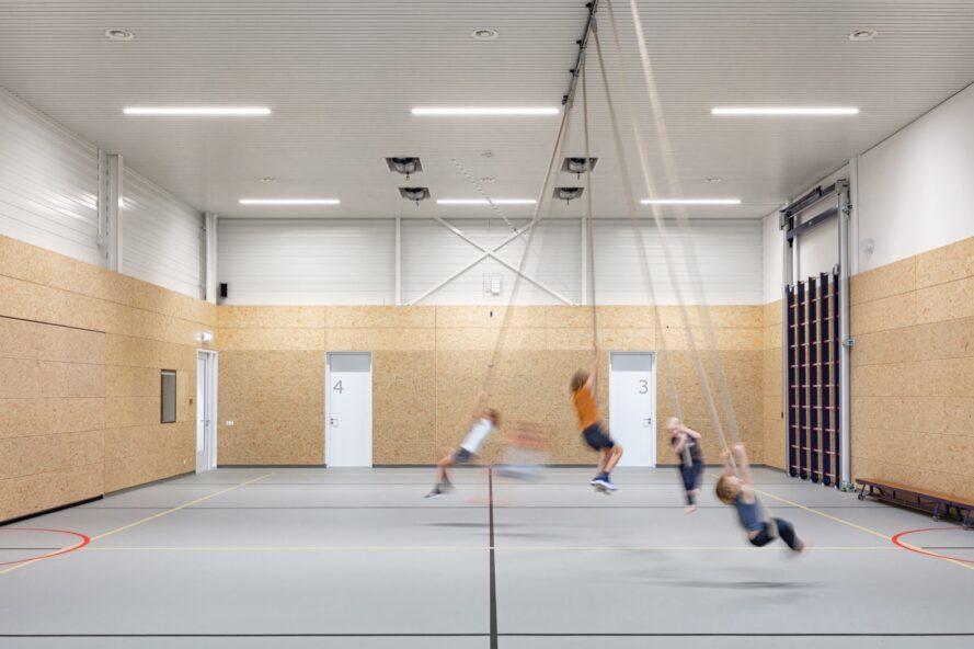 enfants se balançant sur des cordes dans un gymnase