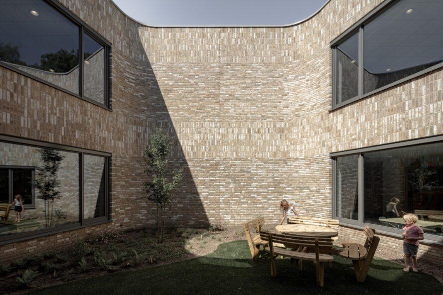 petite cour avec table et chaises en bois entourée de murs de briques d'un bâtiment scolaire