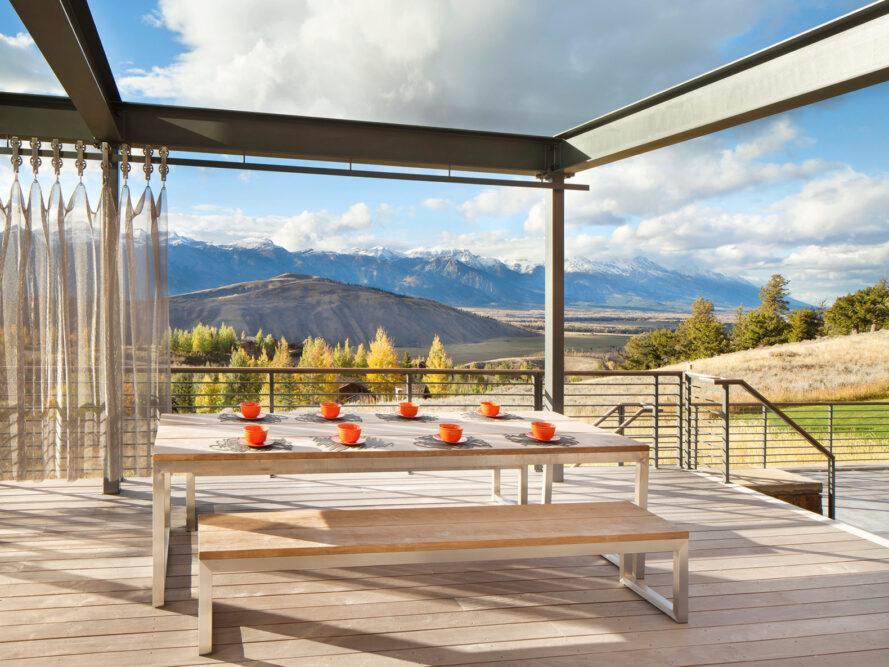 grande table et bancs en bois sur une terrasse en plein air