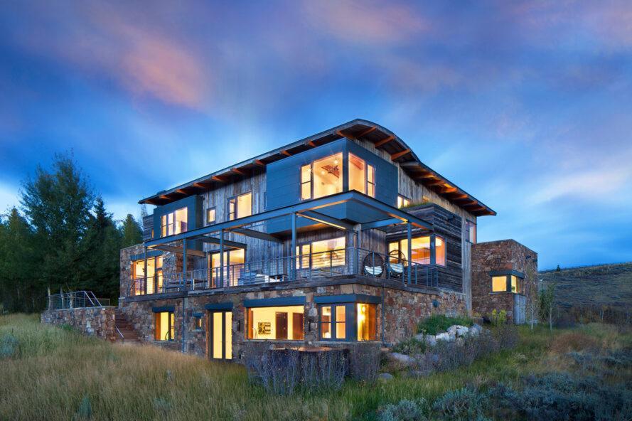 maison de trois étages avec extérieur en bois et en pierre au crépuscule