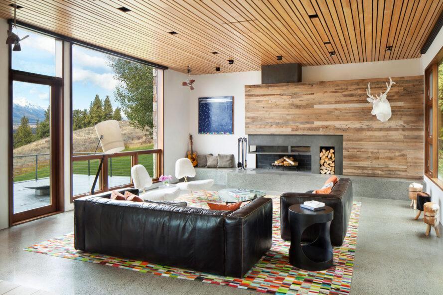 salon avec plafonds et murs en bois et deux canapés en cuir noir face à une cheminée