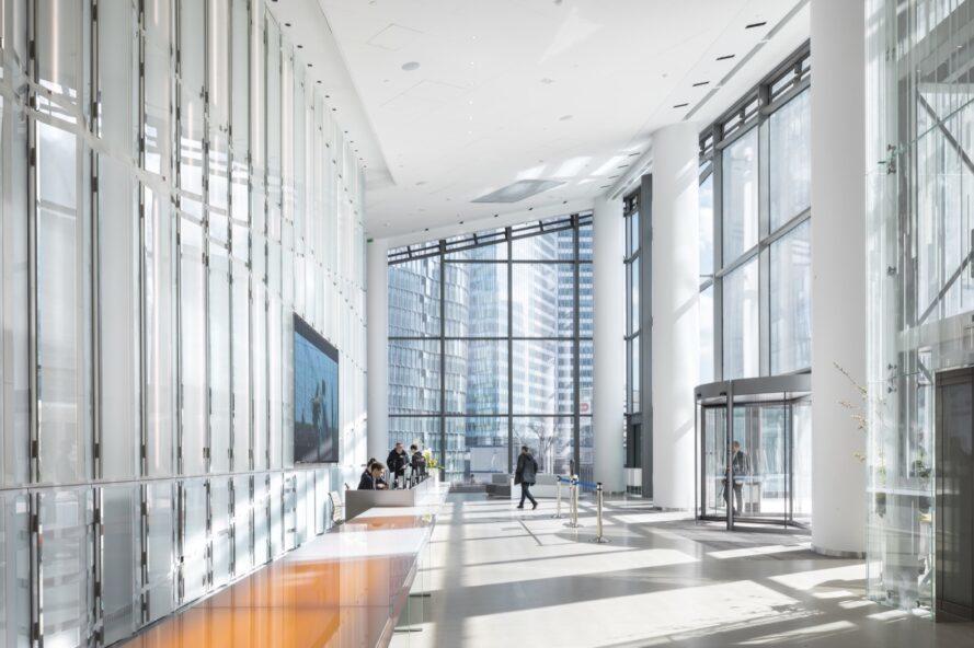 long couloir avec de hauts plafonds et des murs de verre