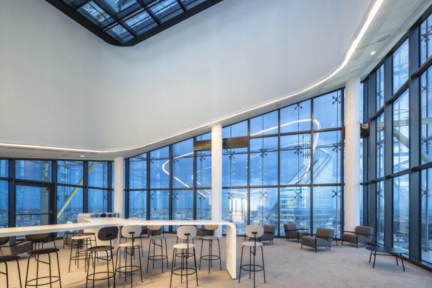 longues tables blanches et chaises hautes dans la salle avec des murs en verre et un plafond en pente