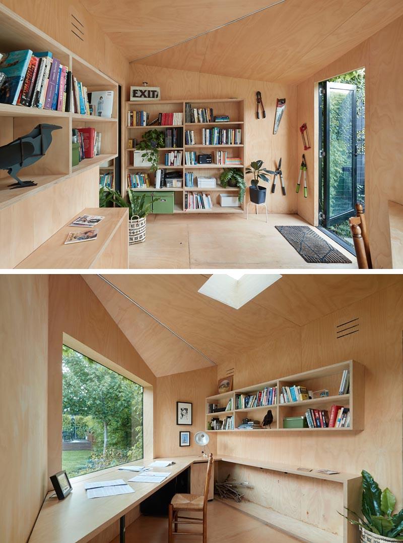 Un petit bureau à domicile a des murs en contreplaqué, des étagères et un grand bureau.
