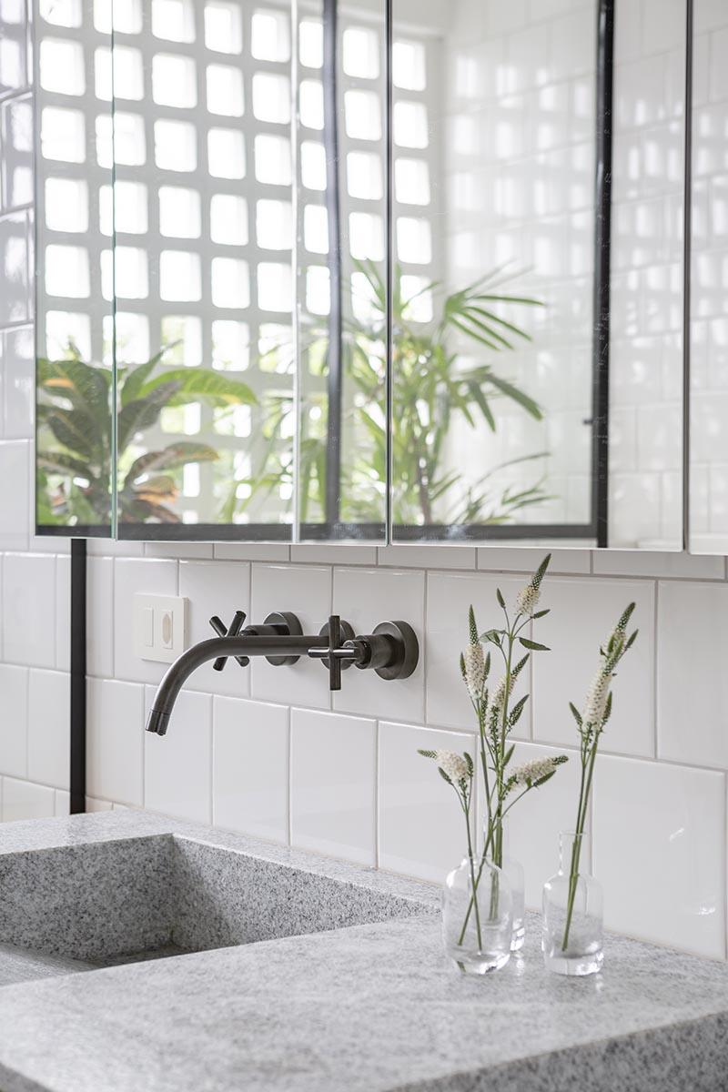 La vanité en bois naturel de cette salle de bain moderne est surmontée d'un granit brésilien gris et blanc nommé
