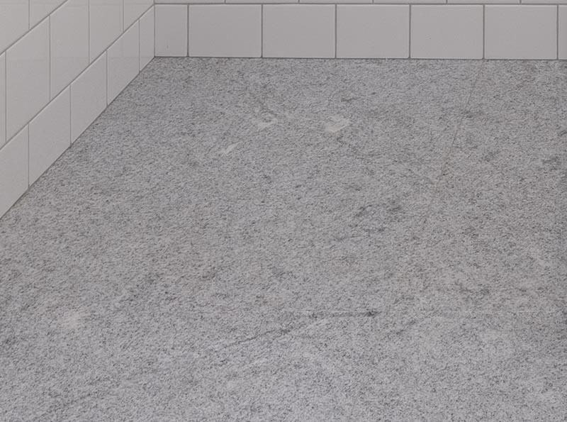 Cette salle de bains moderne dispose d'un sol en pierre naturelle brésilienne.  En utilisant un sol gris, il crée une base neutre pour que les carreaux blancs, la vanité en bois et les accents noirs se démarquent.  #GraniteFloor #GraniteBathroomFloor #GreyFloor #NaturalStoneFloor