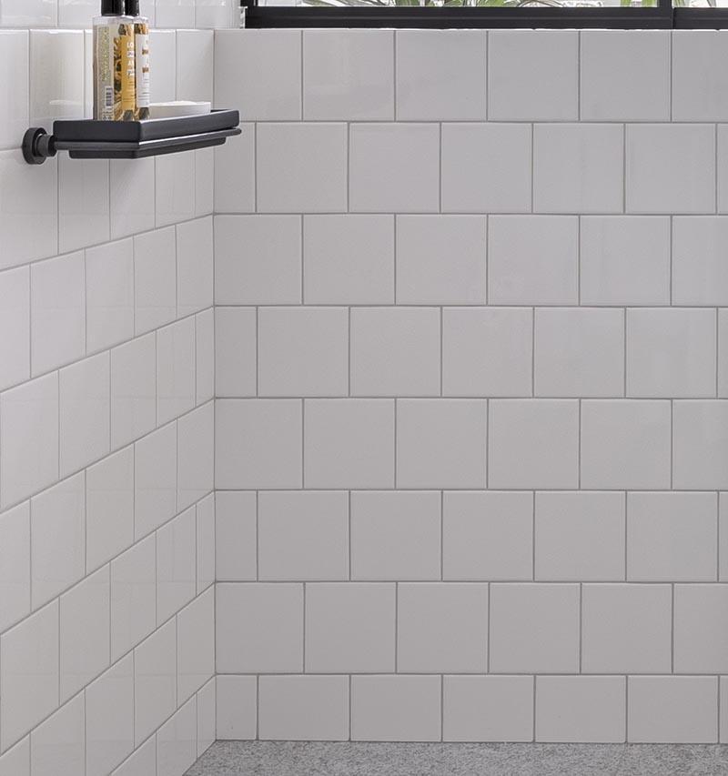 Dans cette salle de bain moderne, des carreaux blancs du sol au plafond recouvrent les murs, mesurent 15x15 cm, ont un coulis blanc assorti.  #SquareWhiteTiles #SquareTiles #BathroomIdeas