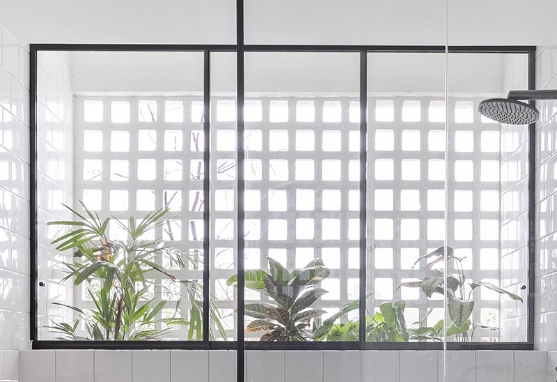Sous la douche de cette salle de bain moderne, il y a une fenêtre à trois volets à cadre noir qui donne sur une collection de plantes situées entre le mur de la salle de bain et la façade de l'appartement.  #BlackFramedWindow #BathroomDesign #PlantIdeas