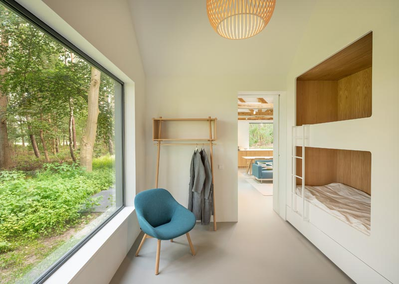 Cette chambre moderne pour enfants dispose de lits superposés doublés de bois et d'une grande baie vitrée.  #BunkBeds #BuiltInBunkBeds #ChildrensRoom #KidsRoom #Windows