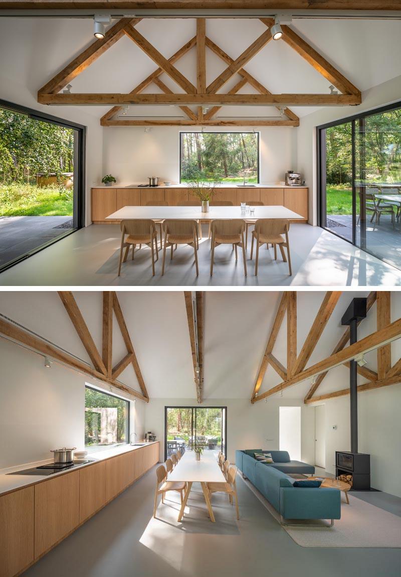 À l'intérieur de cette maison moderne, la cuisine, la salle à manger et le salon minimalistes partagent tous le même espace, tandis que la structure du toit a été laissée apparente.  #OpenPlanInterior #MinimalistKitchen #DiningRoom #ExposedCeiling #LivingRoom #Fireplace
