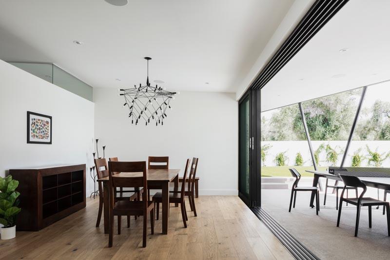 Une salle à manger moderne avec des portes coulissantes en verre empilées, des murs blancs et des meubles en bois sombre.