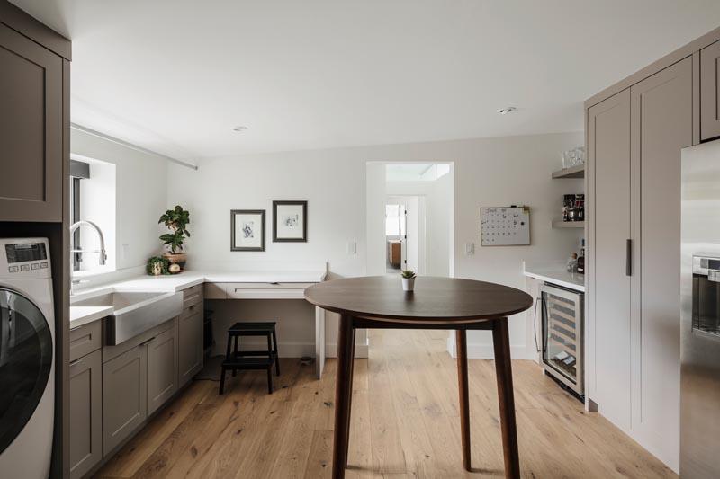 Un cellier et une buanderie modernes qui comprennent un bar, un rangement, un évier de ferme et une laveuse / sécheuse.